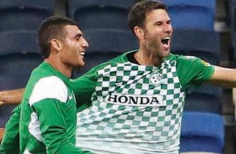 Maccabi Haifa defender Dekel Keinan (right) celebrates after giving his team a 3-2 lead in last night's 4-2 victory over Hapoel Haifa at Haifa Stadium (photo credit: ERAN LUF)