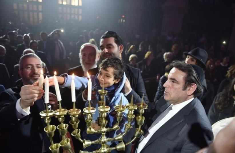 """The families of the victims of the Hyper Cacher terrorist attack (Philippe Braham, Yohan Cohen, Yoav Hattab, and François-Michel Saada) in Paris last year light the Hanukka candles at the """"Let There Be Light"""" - Unity Gathering in Paris (photo credit: ISRAEL BARDUGO)"""