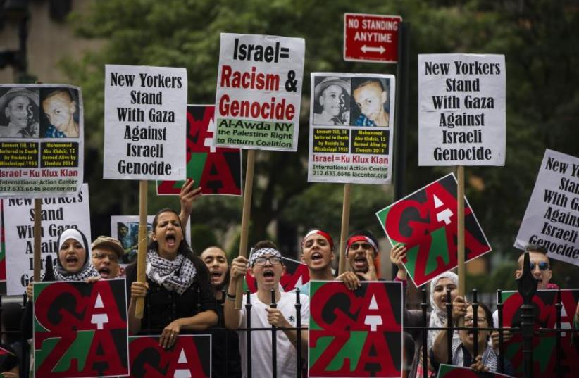 Pro-Palestinian demonstrators display signs outside of New York City hall, where a pro-Israel rally was organised (photo credit: LUCAS JACKSON / REUTERS)