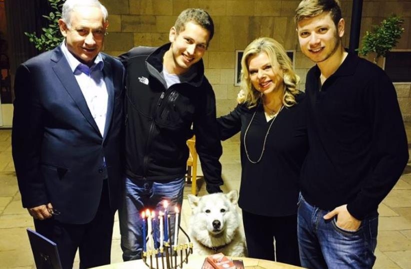 The Netanyahu family poses with dog Kaiya in front Hannuka candles, December 11, 2015 (photo credit: FACEBOOK)