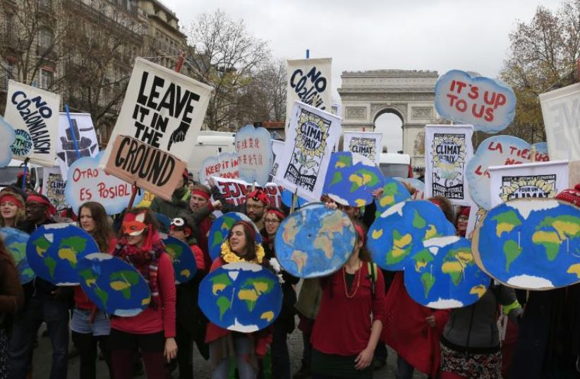 Environmentalists demonstrate near the Arc de Triomphe in Paris, France, as the World Climate Change Conference 2015 (COP21) meets, December 12, 2015 (photo credit: REUTERS)