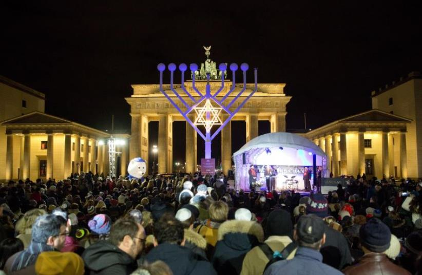 People stand in front of a giant eight- branched candelabrum Menorah in front of the Brandenburg Gate in Berlin on December 6, 2015 at the start of the holiday of the jewish religious festival of lights Hanukkah. (photo credit: AFP PHOTO / DPA / JÖRG CARSTENSEN GERMANY OUT)