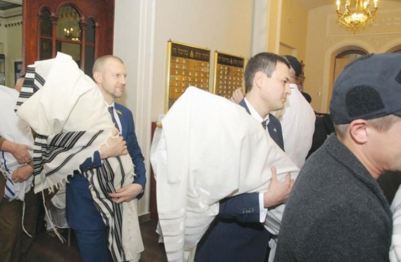 UKRAINIAN OFFICIALS return the Torah scrolls to the Brodsky Choral Synagogue in Kiev on Thursday. (photo credit: ROMAN VILENSKI)