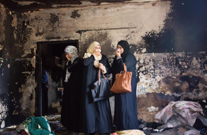 Photo of the Year: Menahem Kahana of the French AFP agency shows three Palestinian women standing in the Dawabsheh family home in the West Bank town of Duma, shortly after the arson that led to the deaths of an 18-month-old baby and his parents. (photo credit: MENAHEM KAHANA)