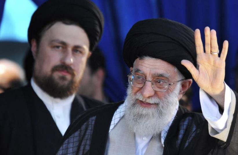 Iran's Supreme Leader Ayatollah Ali Khamenei (R) waves to his supporters as Hassan Khomeini, grandson of Iran's Late Leader Ayatollah Ruhollah Khomeini, looks on during a ceremony to mark the death anniversary of the latter (photo credit: REUTERS)