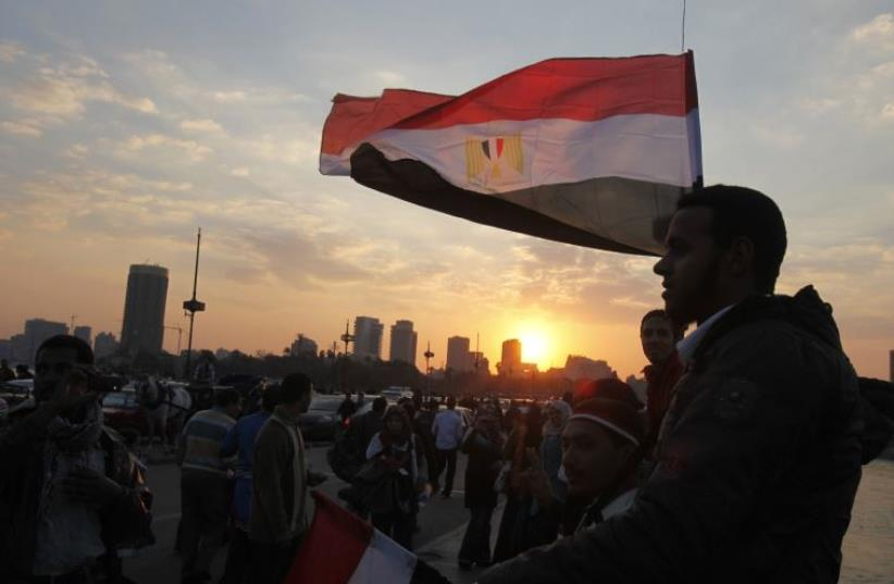 People stand on a bridge overlooking the river Nile as many Egyptians walk on the streets with Egyptian flags in Cairo (photo credit: REUTERS)