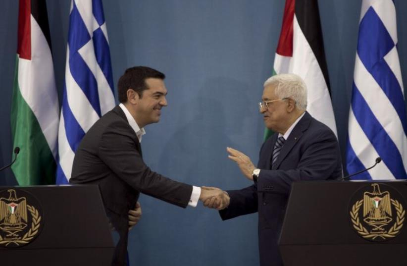 Greek Prime Minister Alexis Tsipras (L) shakes hands with Palestinian Authority President Mahmoud Abbas during a news conference in the West Bank city of Ramallah (photo credit: REUTERS)