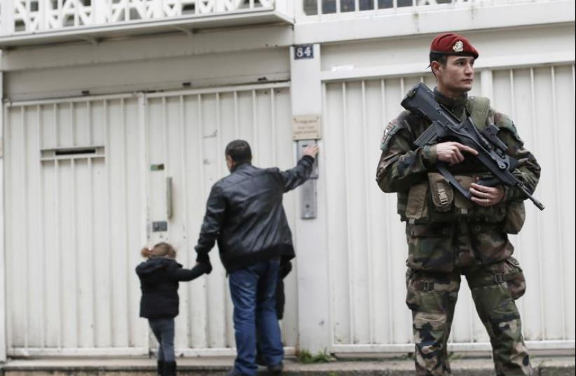 A French soldier secures the entrance to a Jewish school in Paris after the Charlie Hebdo and Hyper Cacher terrorist attacks last January (photo credit: REUTERS)