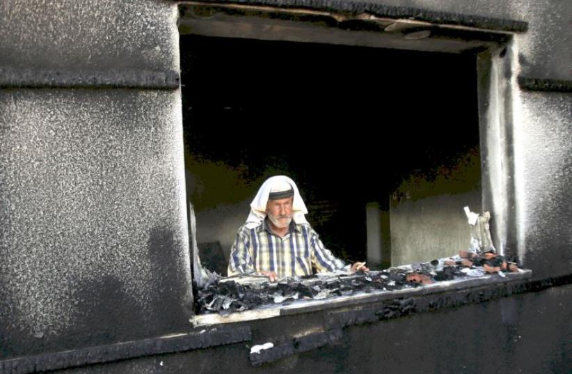 A man looks out of a house badly damaged by a firebomb attack by suspected Jewish extremists in the Palestinian village of Duma in the West Bank, July 31, 2015 (photo credit: REUTERS)