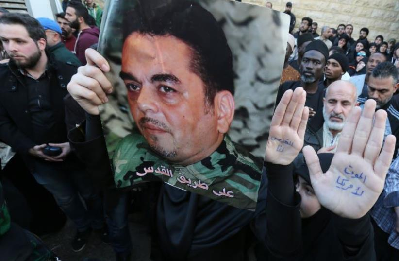 Lebanese mourners hold portraits of Lebanese militant Samir Kantar during his funeral procession (photo credit: AFP PHOTO)