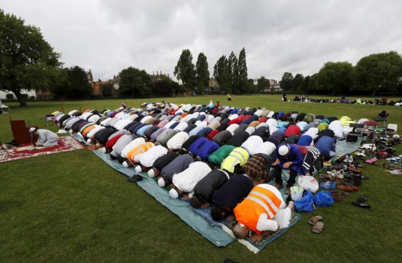 Muslims perform prayers for Eid-al Fitr to mark the end of the holy fasting month of Ramadan at a park in London (photo credit: REUTERS)