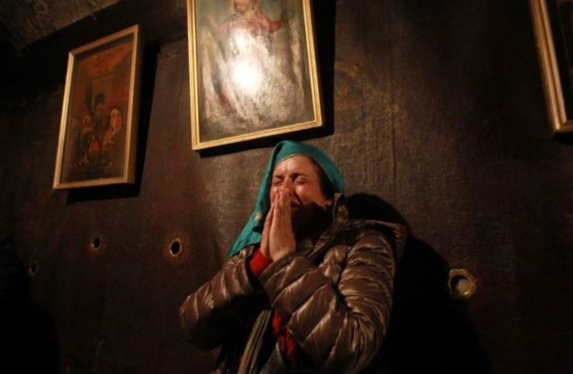 A Christian worshiper prays inside the Grotto at the Church of the Nativity