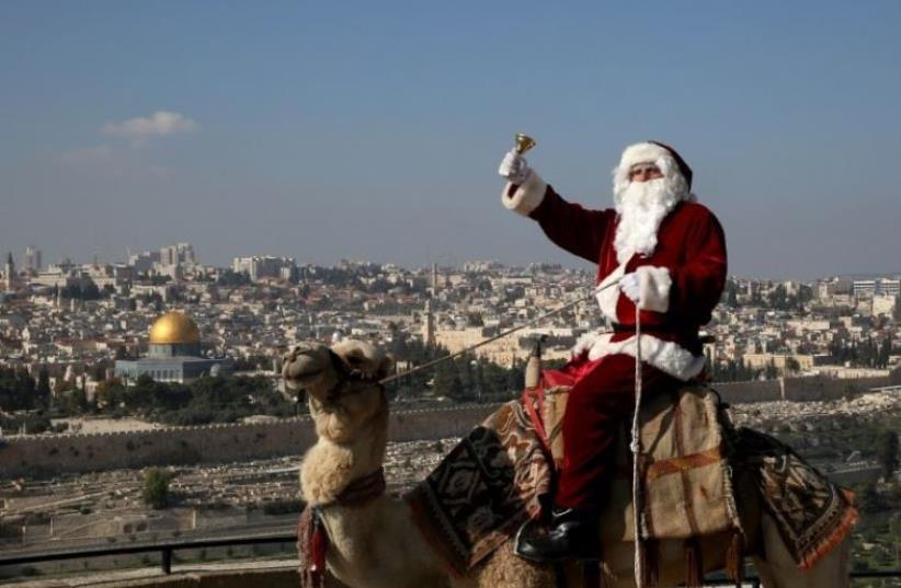 A Christian man dressed up as Santa Claus rings a bell as he sits on a camel at Mt. Olives back-dropped by Jerusalem's Old City skyline (photo credit: AFP PHOTO)