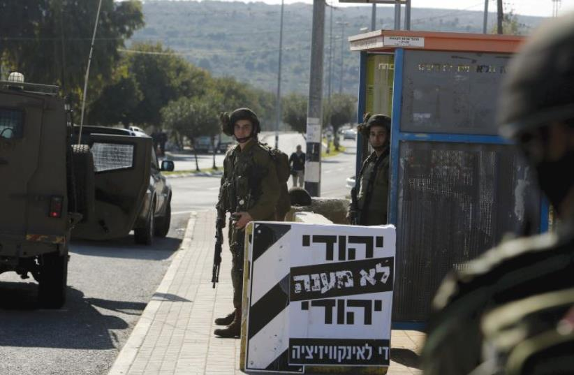 IDF SOLDIERS stand guard next to a poster which reads in Hebrew, 'A Jew doesn't torture a Jew. Enough with the inquisition,' at the entrance to Ariel (photo credit: REUTERS)