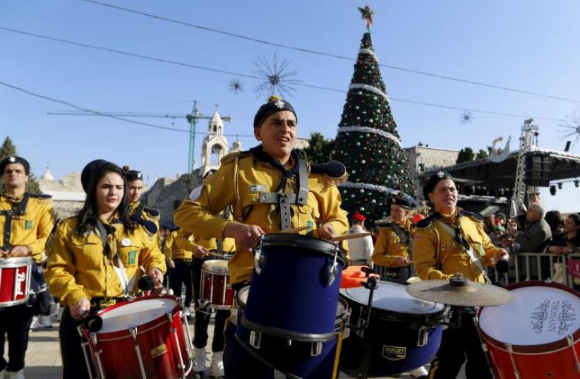 A Palestinian marching band parades during a Christmas procession at Manger Square in the West Bank town of Bethlehem (photo credit: REUTERS)
