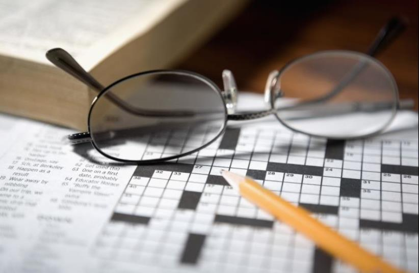 Close-up of a pencil and a pair of eyeglasses on a crossword puzzle (photo credit: INGIMAGE)
