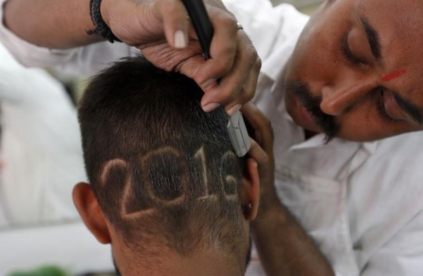 A man gets a haircut depicting 2016 at a barbershop in Ahmedabad, India