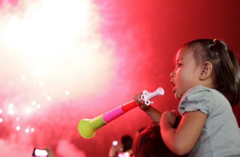 A girl blows a party horn at midnight during New Year celebrations in Manila, Philippines