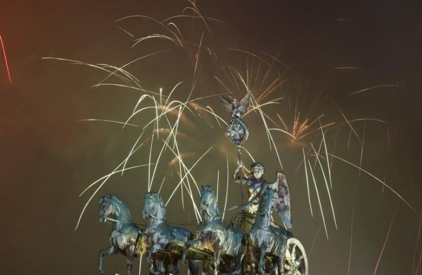 Fireworks explode next to the Quadriga sculpture atop the Brandenburg gate