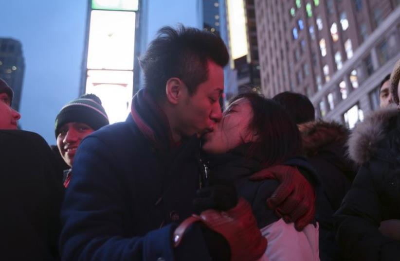 A couple kiss on the ground in a penned off area of Times Square before New Year's Eve celebrations
