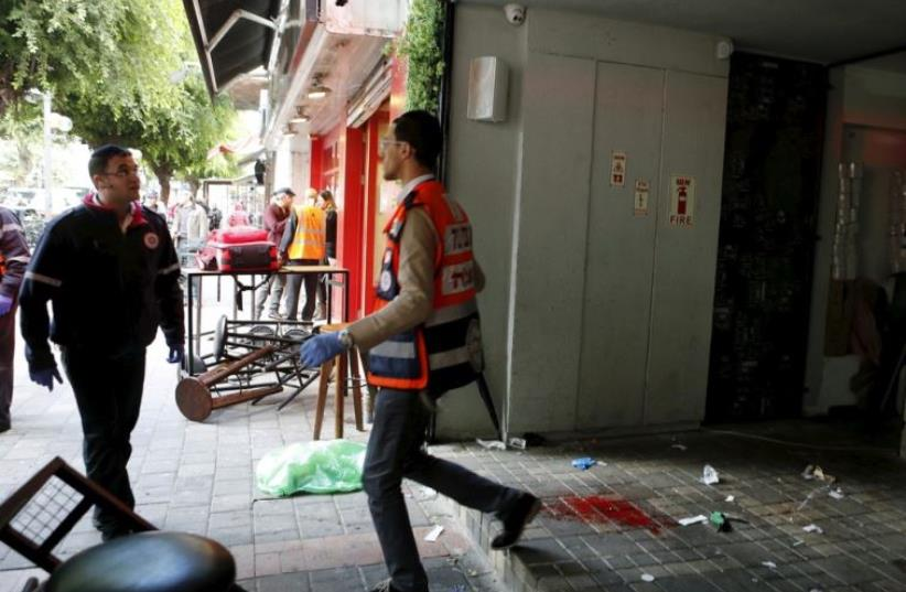 Rescue personnel walk next to blood stains at the scene of a shooting incident in Tel Aviv
