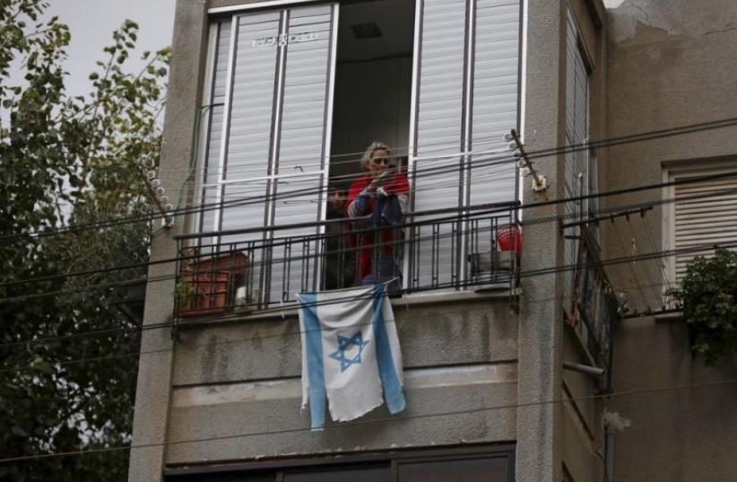 An Israeli flag hangs on a balcony rail as a woman looks at the scene of a shooting incident in Tel Aviv (photo credit: REUTERS)