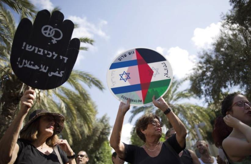 Left - wing protesters hold placards during a demonstration in Tel Aviv (photo credit: REUTERS)