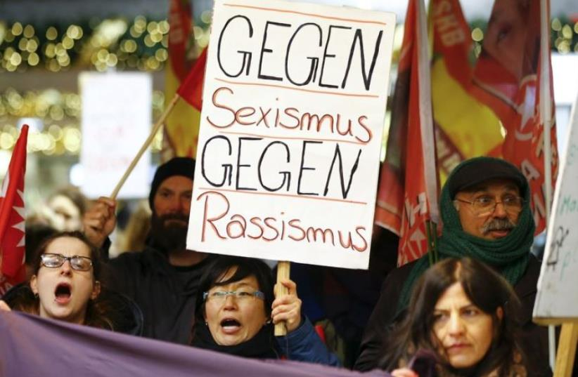 """Women shout slogans and hold up a placard that reads """"Against Sexism - Against Racism"""" as they march through the main railway station of Cologne, Germany (photo credit: REUTERS)"""