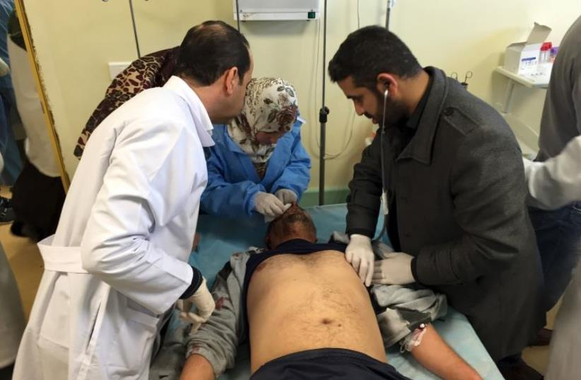 An injured man receives treatment inside a hospital in Misurata, Libya January 7, 2016 after one of Libya's worst truck bombs in years exploded at a police training center in the town of Zliten.  (photo credit: REUTERS)