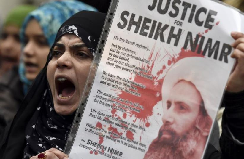 A protester holds a placard during a demonstration against the execution of Shi'ite cleric Sheikh Nimr al-Nimr in Saudi Arabia, outside the Saudi Arabian Embassy in London, Britain, January 3, 2016 (photo credit: REUTERS/TOBY MELVILLE)