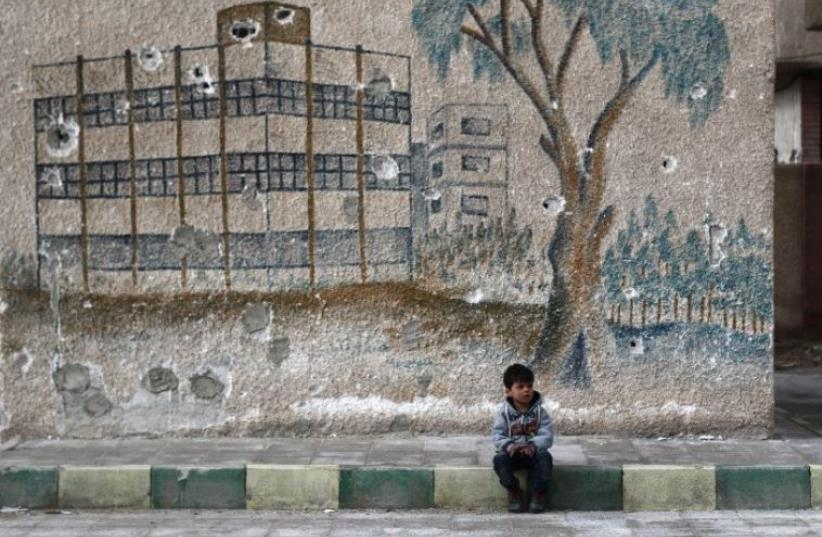 A Syrian child sits in front of a mural covered in bullet holes on the wall of a former school in the rebel-held region of Eastern Ghouta (photo credit: AFP PHOTO)