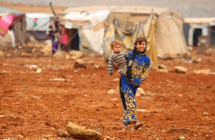 An internally displaced Syrian youth carries a baby inside a refugee camp in the Hama countryside (photo credit: REUTERS)