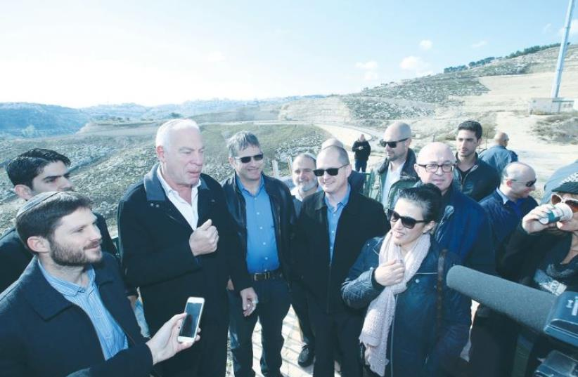 AGRICULTURE MINISTER Uri Ariel speaks at the E1 site in Ma'aleh Adumim yesterday, surrounded by members of the Knesset's Land of Israel Caucus. (photo credit: MIRI TZAHI)