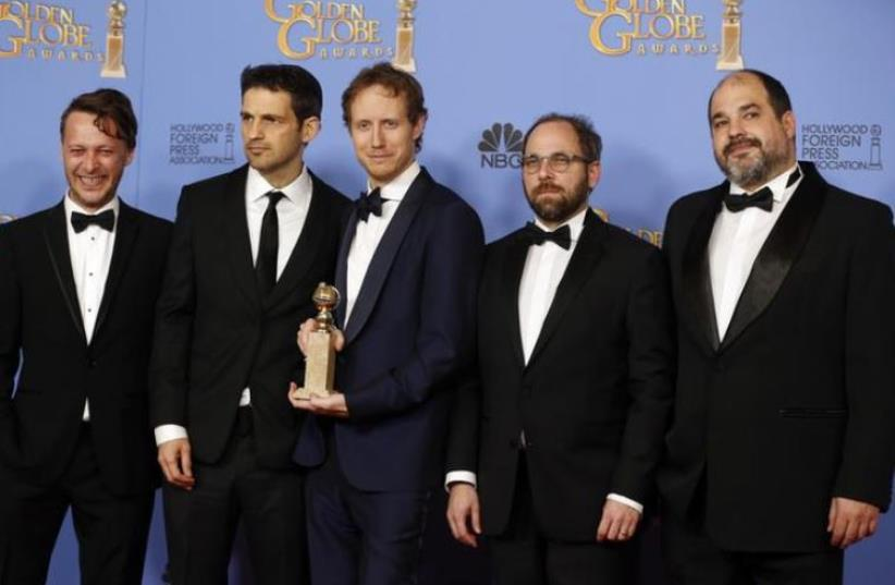 "Director Laszlo Nemes (C) poses with the award for Best Motion Picture - Foreign Language for the Hungarian film ""Son of Saul"" with the film's star Geza Rohrig (2nd L) and other crew during the 73rd Golden Globe Awards in Beverly Hills, California January 10, 2016.  (photo credit: REUTERS)"