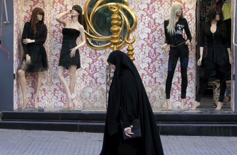 Woman wearing an abaya walks past a fashion clothing store in Lebanon (photo credit: REUTERS)
