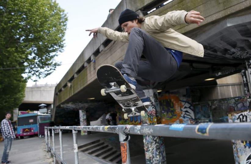 A skateboarder performs a jump over a railing (photo credit: REUTERS)