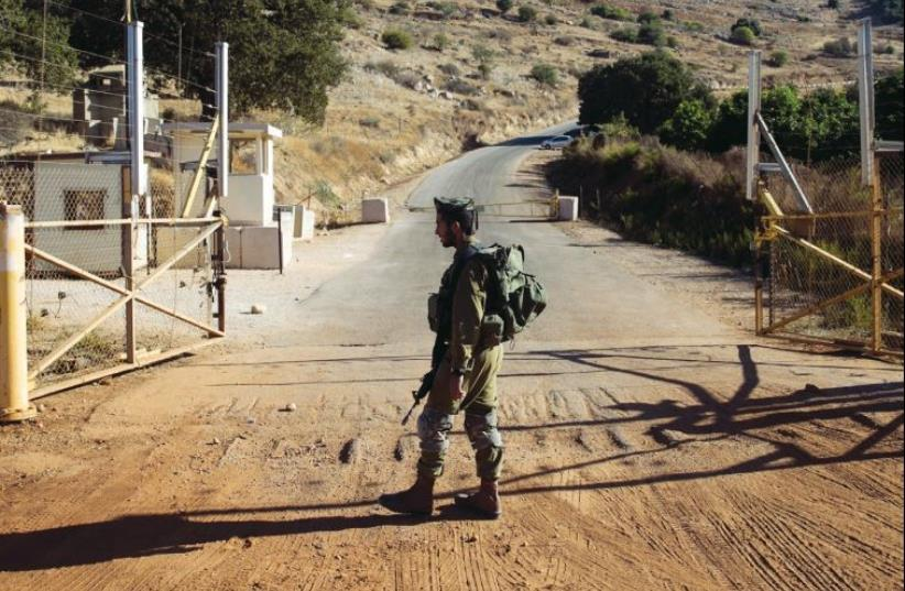 An IDF soldier stands guard at a check point near the Lebanese- Israeli border, in October 2014 (photo credit: REUTERS)