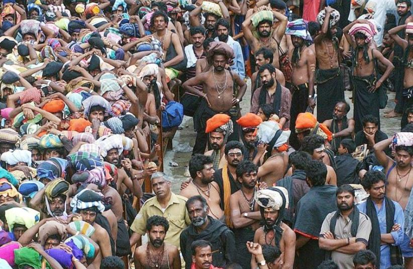 Hindu devotees wait outside the Sabarimala Temple to offer prayers for the Hindu god 'Ayyappa' in Pathanamthitta in the southern Indian state of Kerela November 20, 2002.  (photo credit: REUTERS)