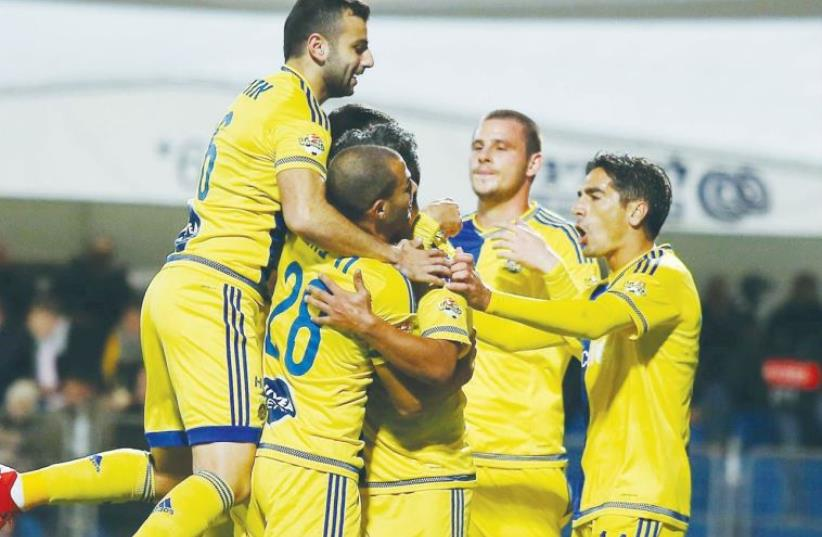 Maccabi Tel Aviv players celebrate after securing their place in the State Cup last-16 (photo credit: ADI AVISHAI)
