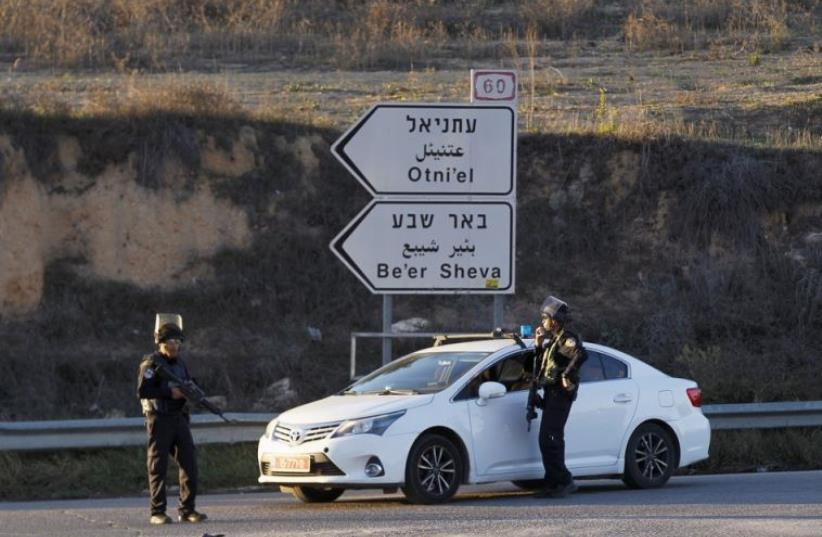 Israeli policemen stand near a checkpoint close to the West Bank settlement of Otniel (photo credit: REUTERS)