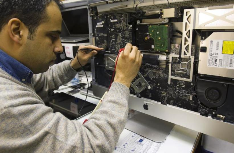 A man repairs an iMac in a shop at a mobile and computer shopping complex in northern Tehran January 18, 2011 (photo credit: REUTERS)