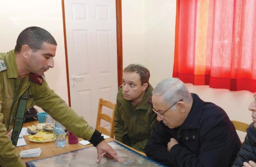 PRIME MINISTER Benjamin Netanyahu and Defense Minister Moshe Ya'alon get a security briefing during their visit to Otniel yesterday. (photo credit: AMOS BEN GERSHOM, GPO)