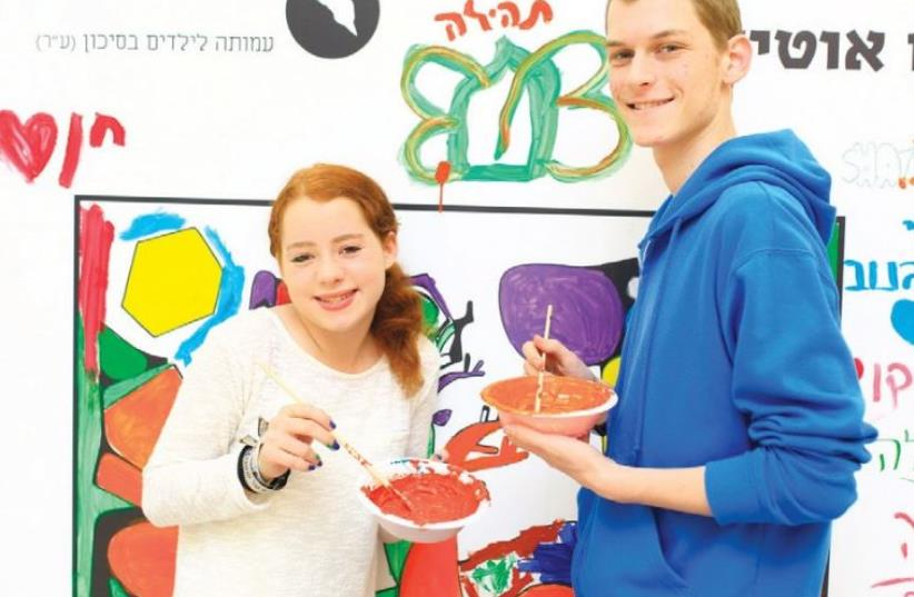 STUDENTS DAB PAINT onto a large coloring wall yesterday as part of a campaign launched by the ALUT organization to raise awareness and funds. (photo credit: Courtesy)