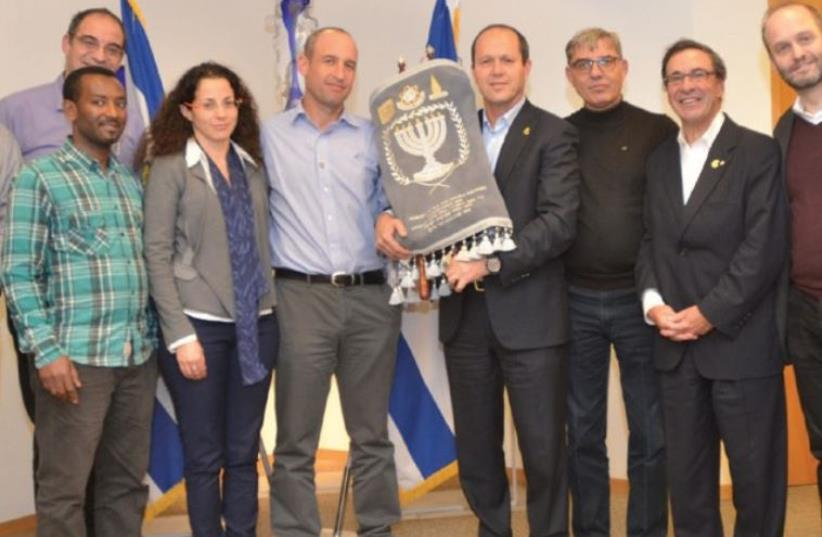 JERUSALEM MAYOR Nir Barkat holds a Torah that was donated in honor of Shira in a ceremony at the capital's City Hall yesterday. (photo credit: JEKI LEVI)