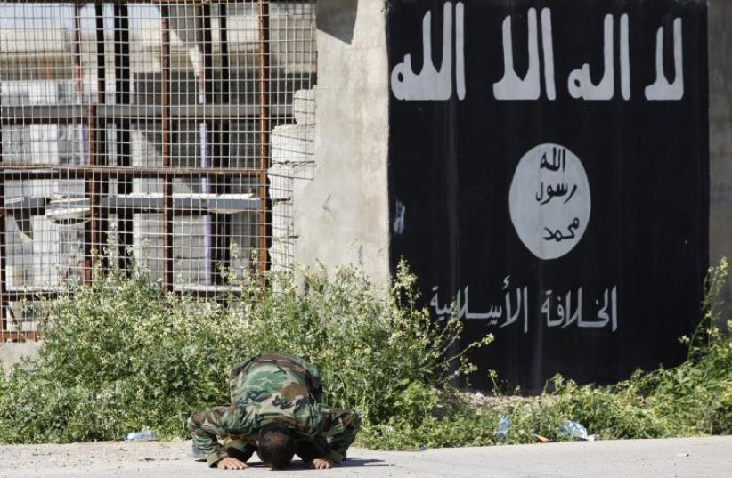 A member of a militia kneels as he celebrates victory next to a wall painted with the black flag commonly used by ISIS militants (photo credit: REUTERS)