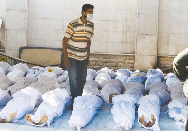 Syrian activists inspect the bodies of people they say were killed by nerve gas in the Ghouta region, in the Duma neighborhood of Damascus on August 21, 2013 / Reuters