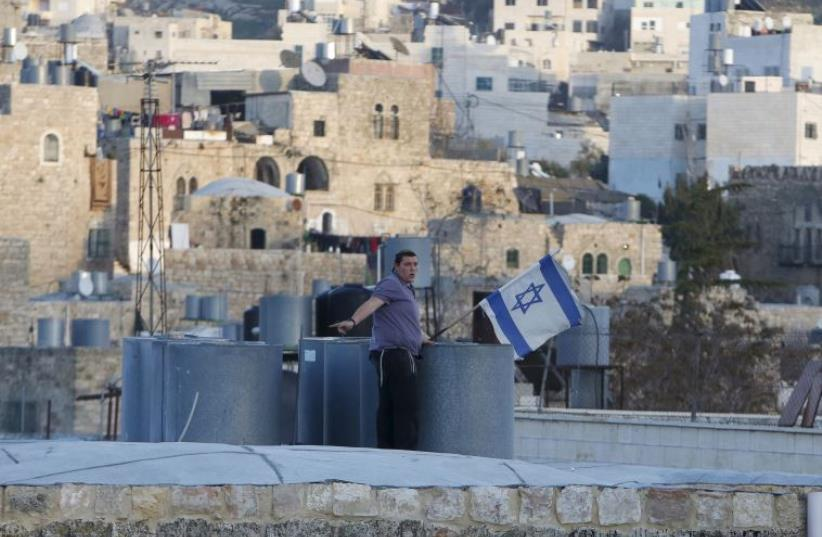 An Israeli settler puts up an Israeli flag over a house, which is disputed between Palestinians and Israelis, in Hebron (photo credit: REUTERS)