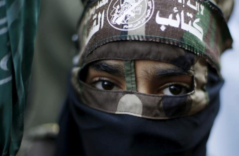 A masked Palestinian boy wearing the headband of Hamas's armed wing takes part in a rally marking the 28th anniversary of Hamas' founding in Gaza City (photo credit: REUTERS)