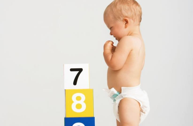 A baby playing (illustrative) (photo credit: INGIMAGE)