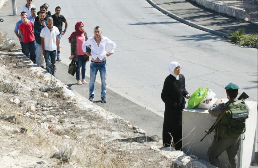 Arab residents are searched by soldiers as they pass through a checkpoint during the height of stabbing attacks in Jerusalem (photo credit: MARC ISRAEL SELLEM/THE JERUSALEM POST)